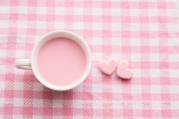 Kopje melk en hartvorm op roze tafelkleed, valentijnsdag achtergrond.