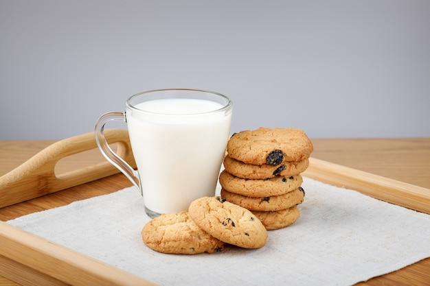 Kopje melk en koekjes met rozijnen op een houten dienblad