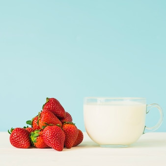 Kopje melk en verse rode aardbeien op tafelblad