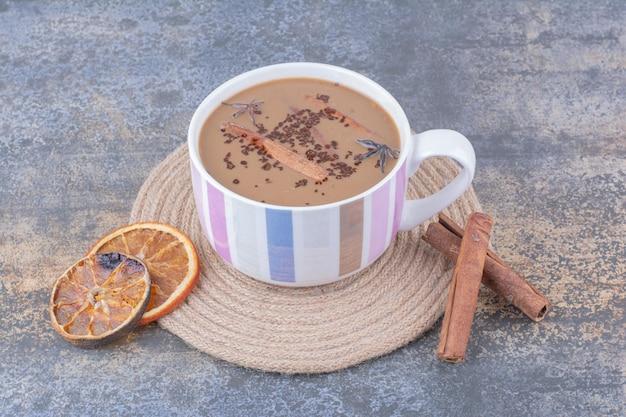 Kopje melkkoffie met kaneelstokjes en stukjes sinaasappel. hoge kwaliteit foto