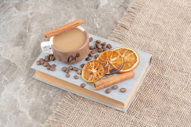 Kopje melkkoffie met koffiebonen en stukjes sinaasappel op boek.