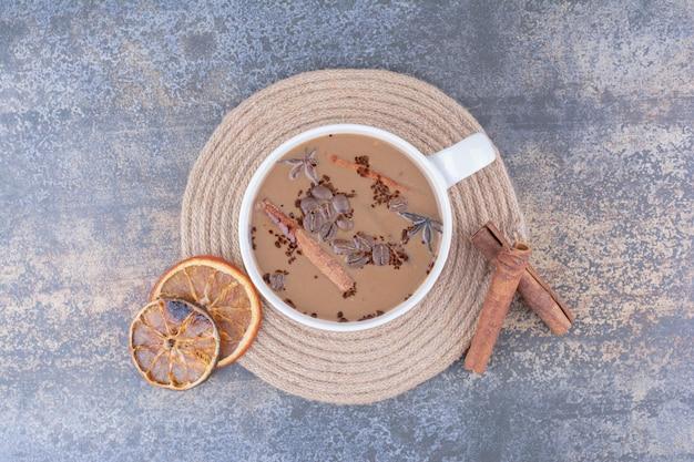 Kopje melkkoffie met pijpjes kaneel en stukjes sinaasappel.