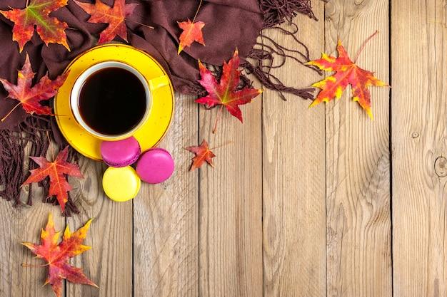 Kopje met zwarte koffie, gele, paarse bitterkoekjes, textiel sjaal, houten tafel met herfst gevallen oranje bladeren