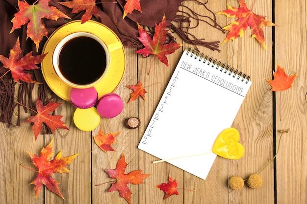 Kopje met zwarte koffie, lolly, bitterkoekjes, textielsjaal, kladblok, houten tafel met gevallen herfstblaadjes plat leggen
