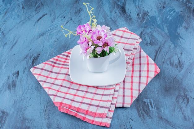 Kopje natuurlijke paarse bloemen met bladeren op blauw.