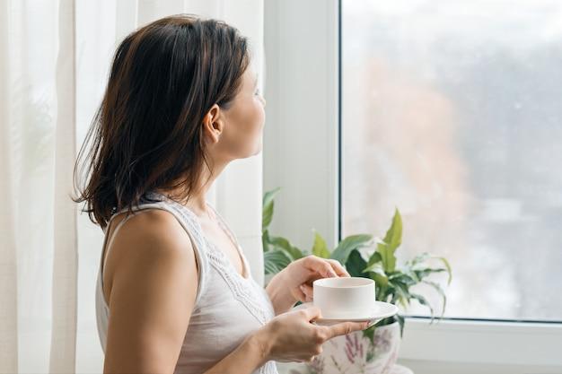 Kopje ochtend verse koffie in de handen van de vrouw