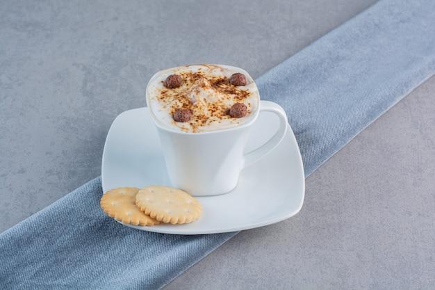 Kopje schuimige warme koffie en koekjes op stenen achtergrond.