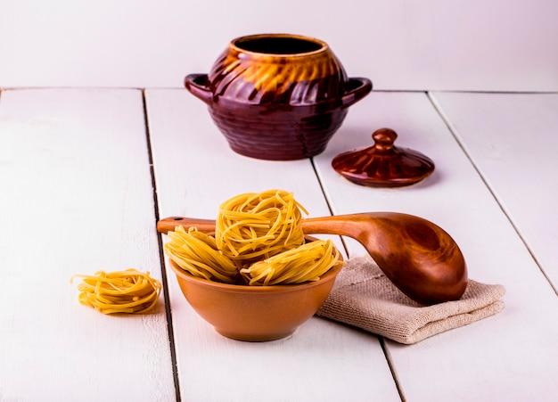 Kopje spaghetti en een houten lepel op een achtergrond van een kleivat op een houten witte tafel