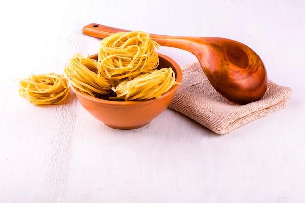 Kopje spaghetti en een houten lepel op een houten witte tafel