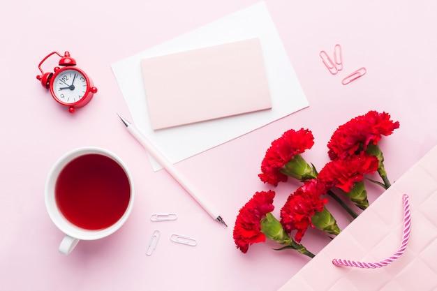 Kopje thee, anjer bloemen kladblok voor tekst op pastel roze achtergrond.