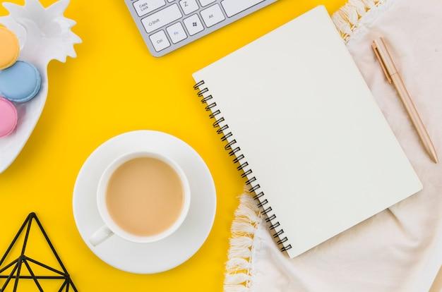 Kopje thee; bitterkoekjes; spiraal notitieboekje; pen op tafellaken tegen gele achtergrond