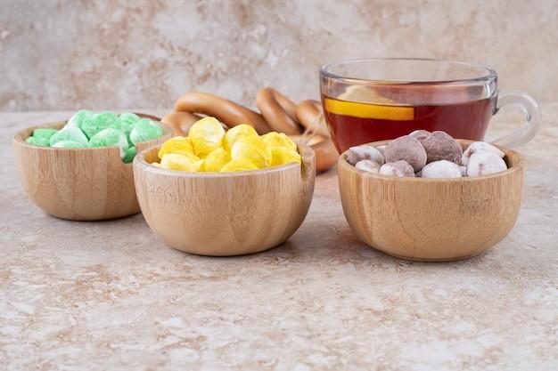 Kopje thee, crackers en kommen snoep op marmeren oppervlak