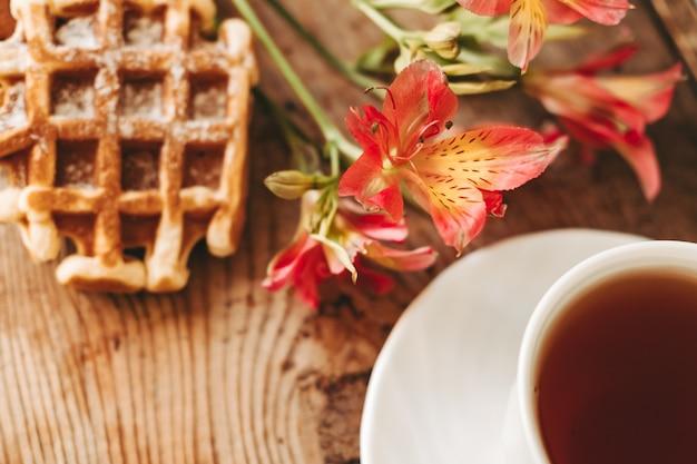 Kopje thee en bloemen. alstroemeria en een kopje thee. weense wafels op een houten ondergrond. ontbijt. mooi stilleven