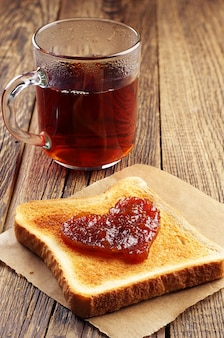 Kopje thee en brood met jam in de vorm van hart
