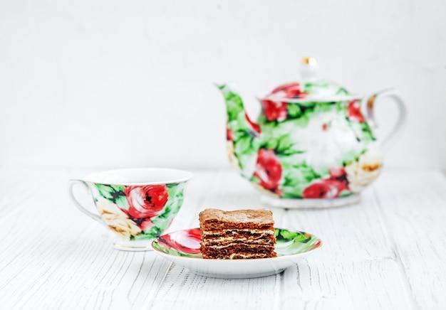 Kopje thee en cake op een houten tafel.