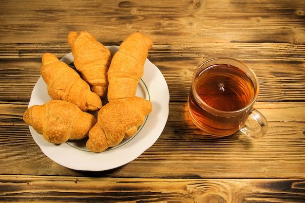 Kopje thee en croissants op houten tafel
