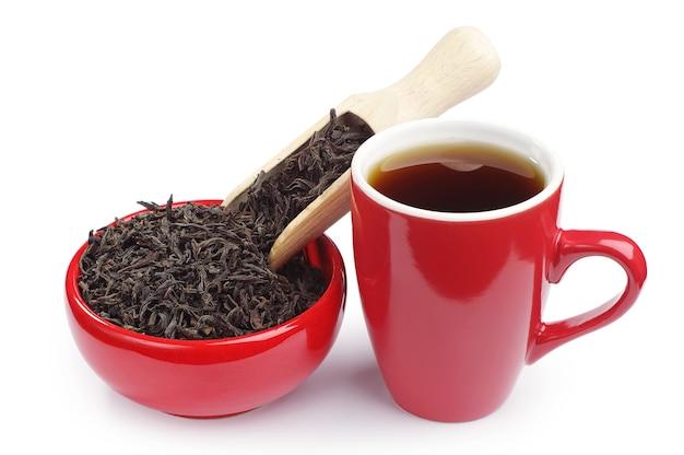 Kopje thee en droge zwarte thee in een rode kom met een houten lepel op wit