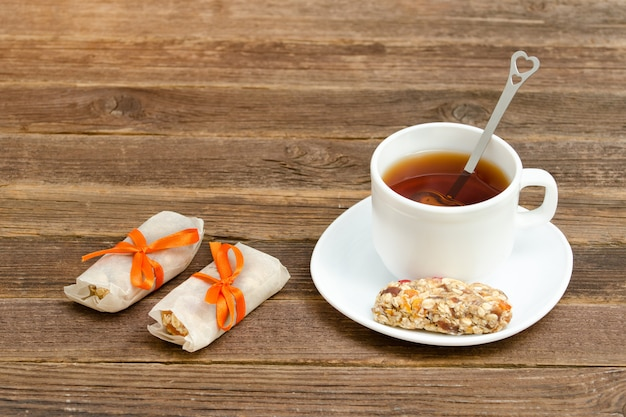 Kopje thee en enkele reep muesli. bruine houten tafel