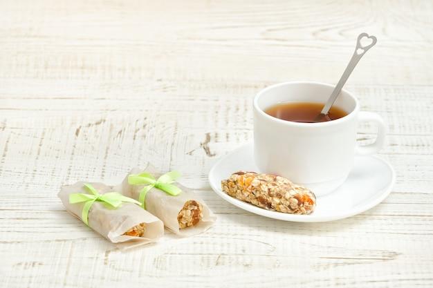 Kopje thee en enkele reep muesli. witte houten tafel