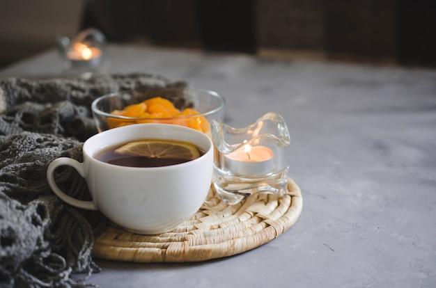 Kopje thee en gedroogde abrikozen op een tafel, kaarsen en gebreide deken.
