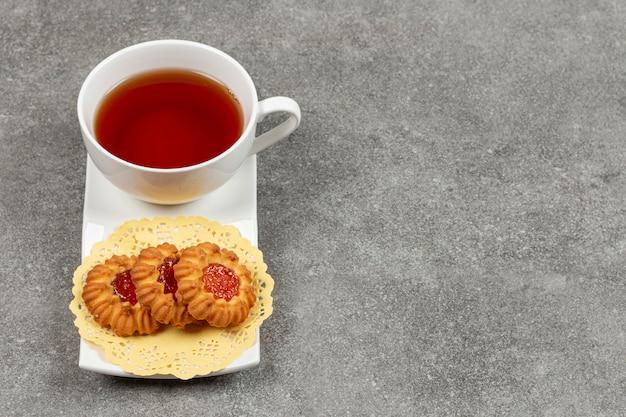Kopje thee en gelei koekjes op schotel