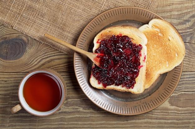 Kopje thee en geroosterd brood met jam op een houten tafel