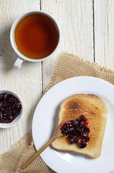 Kopje thee en geroosterd brood met jam op een lichte houten tafel, bovenaanzicht