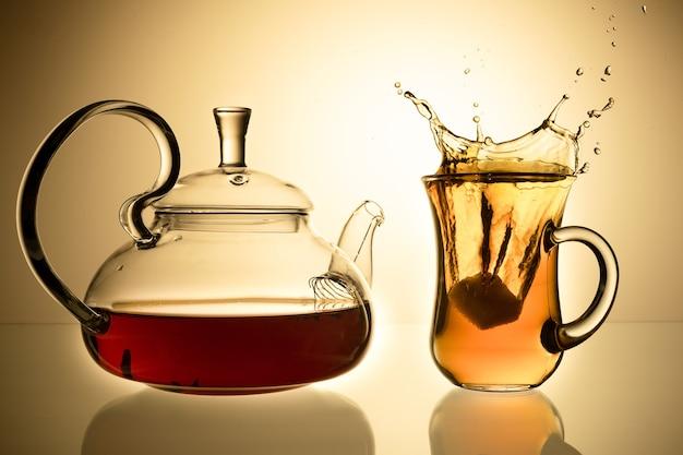 Kopje thee en glazen theepot op glas met oranje achtergrond.