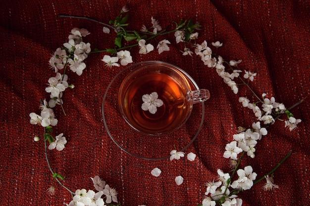 Kopje thee en kersenbrunches op tafel. lente natuur achtergrond met mooie bloesem. thee en bloemen van kers op rode gezellige achtergrond. bovenaanzicht, spandoek. lente concept