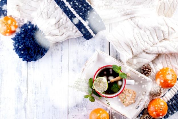 Kopje thee en limoen en munt op een wit dienblad met mandarijnen