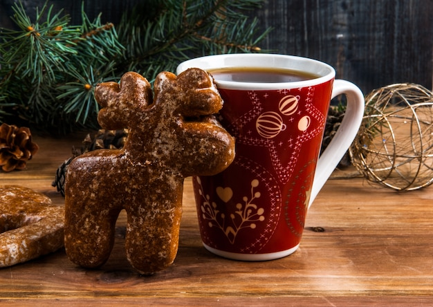 Kopje thee en peperkoek in de vorm van een hert op een houten tafel. in de buurt van de kerstboomtak, dennenappels en kerstballen.