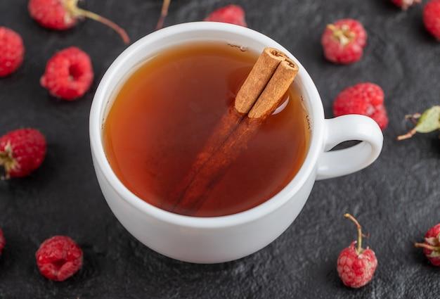Kopje thee en verse frambozen op zwarte tafel.