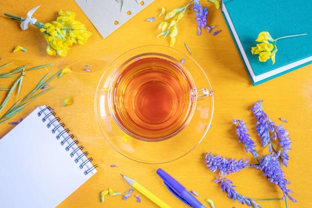 Kopje thee in een transparante beker met een schotel, notebook, pen, potlood, wilde bloemen en kruiden op een gele houten achtergrond.