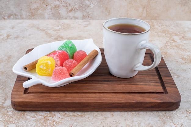 Kopje thee, kaneel en marmelade snoepjes op een houten bord