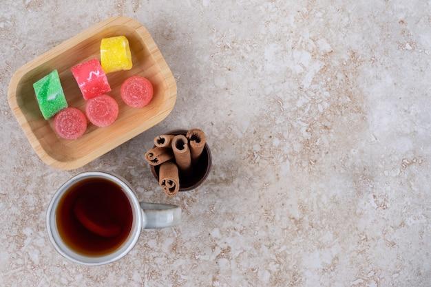 Kopje thee, kaneelstokjes en marmeladesuikergoed op marmeren oppervlak