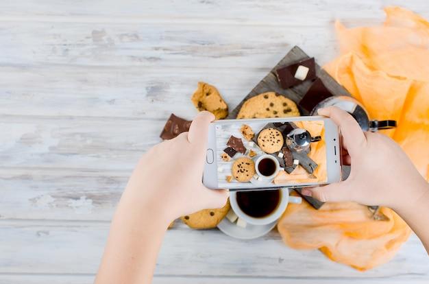 Kopje thee, koekjes op witte houten tafel aan fotogryfirovat eten op telefoon