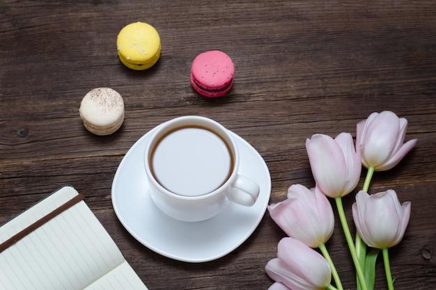 Kopje thee, macarons, roze tulpen en notebook