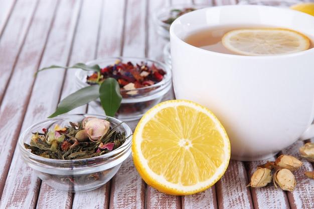 Kopje thee met aromatische droge thee in kommen op houten achtergrond