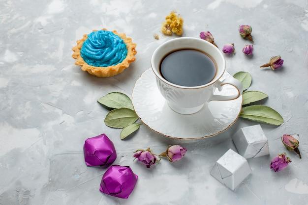 Kopje thee met blauwe crème taart chocolade snoepjes op witgrijs bureau, koekje zoet snoep