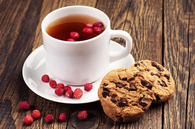 Kopje thee met bosaardbeien en zoete chocoladekoekjes