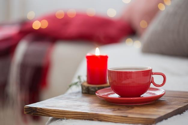 Kopje thee met brandende kaarsen thuis