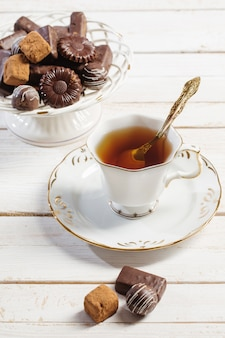 Kopje thee met chocolade snoep op witte houten tafel