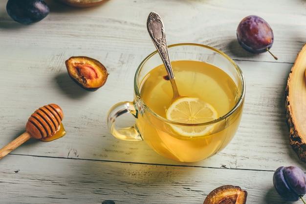 Kopje thee met citroen, honing en gember over houten oppervlak