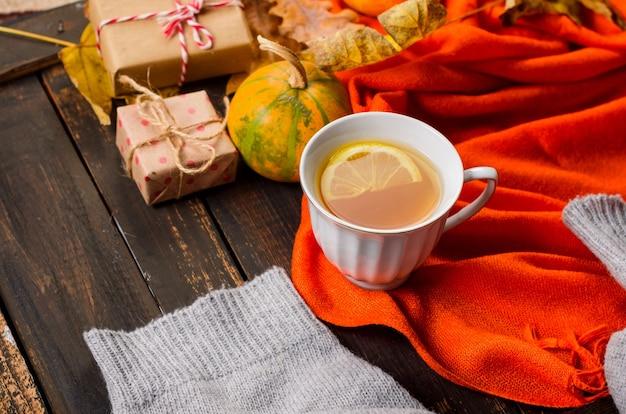 Kopje thee met citroen op houten donkere tafel met herfstbladeren, pompoenen. herfstdecor, herfststemming, herfststilleven. herfst seizoen concept. thanksgiving en halloween vakantie. plat leggen, ruimte kopiëren Premium Foto
