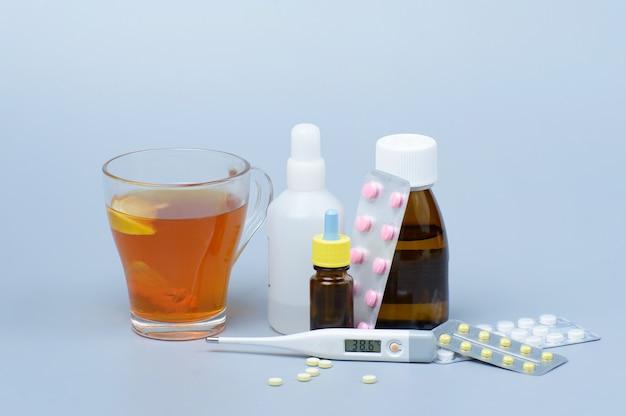 Kopje thee met citroen, thermometer en drugs