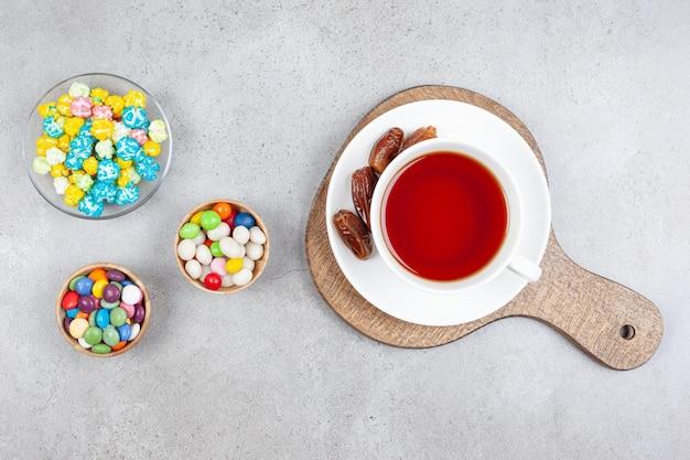 Kopje thee met dadels op een houten bord door houten kommen met verschillende snoepjes op een marmeren oppervlak.