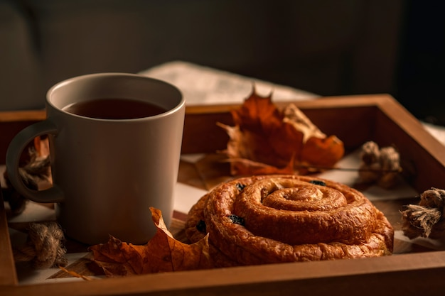 Kopje thee met gebak en herfstbladeren op dienblad