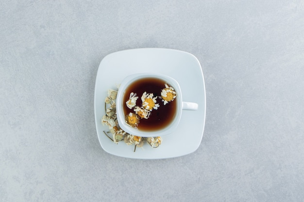 Kopje thee met gedroogde kamille bloemen.
