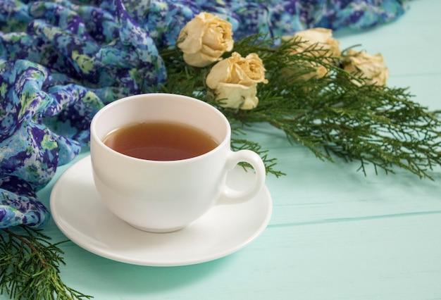 Kopje thee met gedroogde rozen en takken van jeneverbes op een turkooise achtergrond