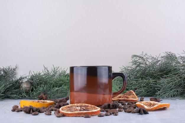 Kopje thee met gedroogde stukjes sinaasappel en verspreide koffiebonen op witte ondergrond